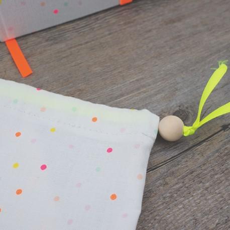 Pochon du même tissu que la couverture du carnet. Fermeture à l'aide d'une perle de bois brute
